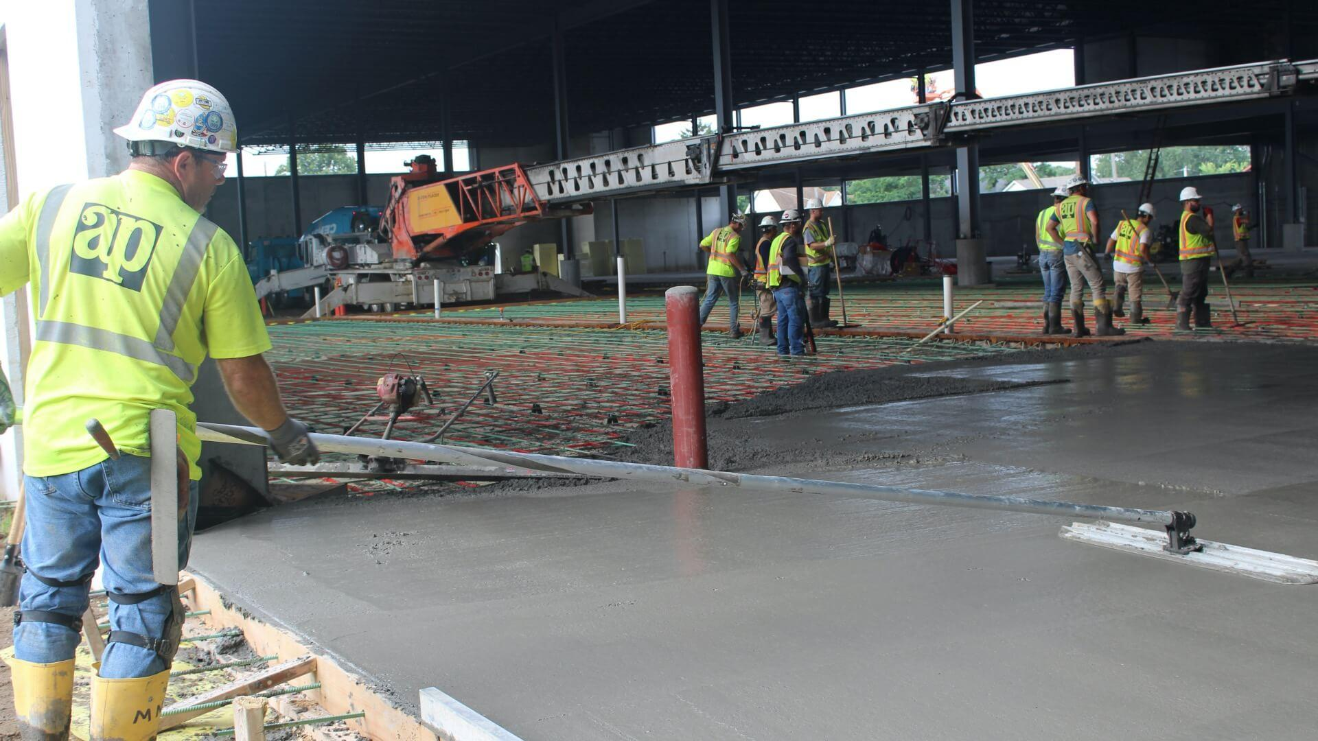 Contractors smoothing out concrete