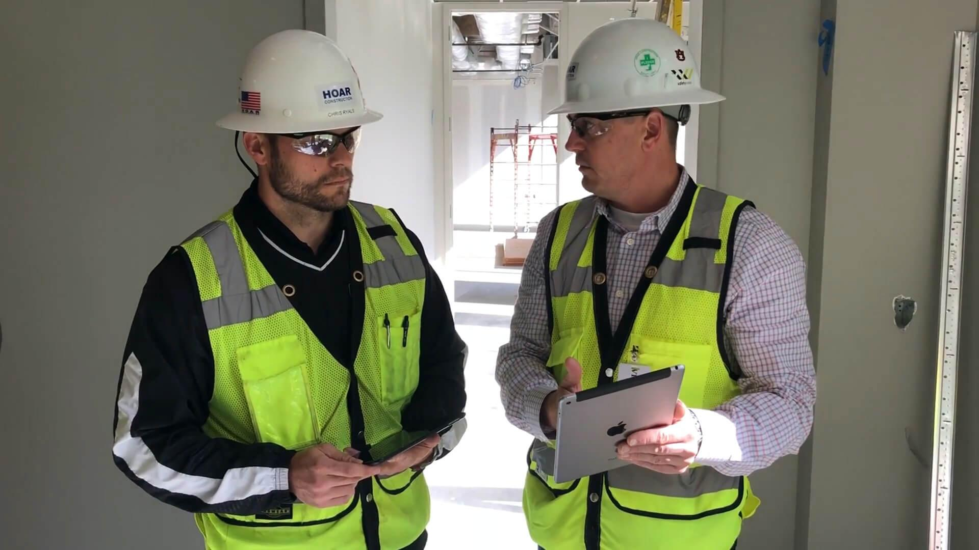 Contractors collaborating over Procore on a tablet