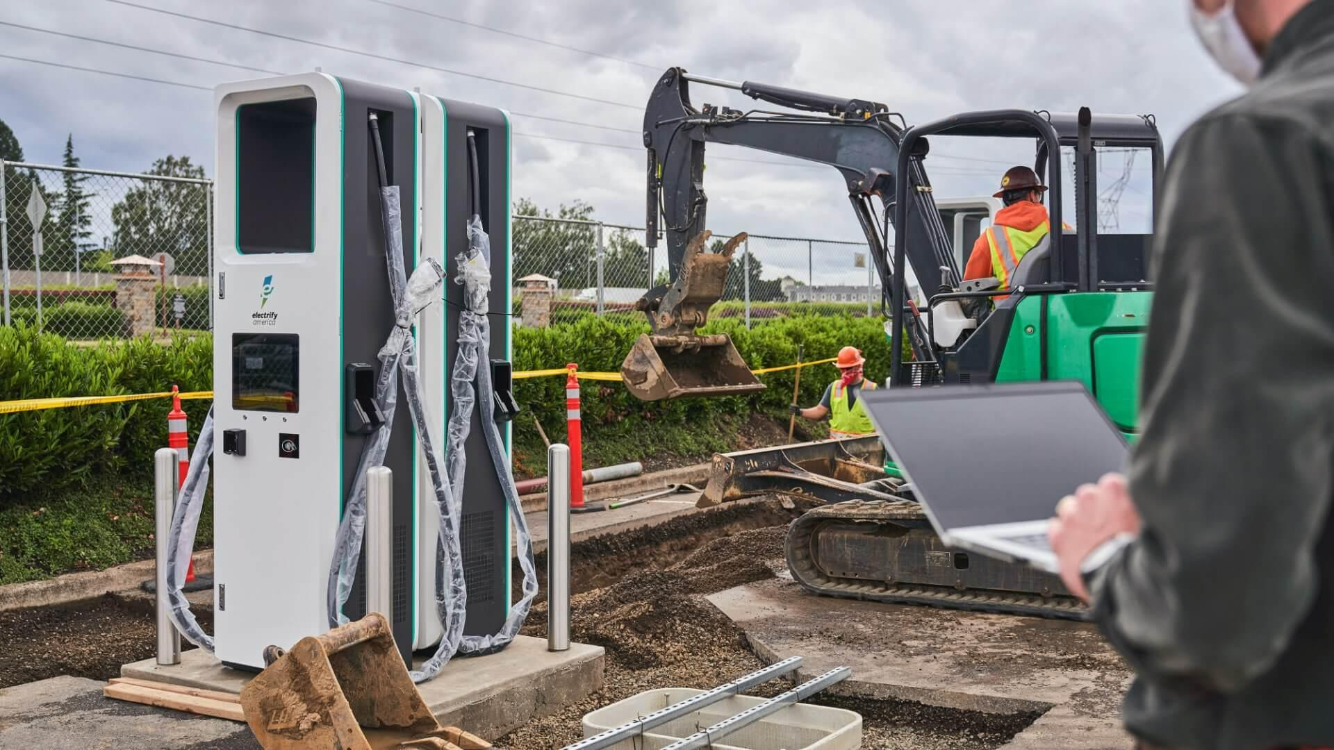 Workers installing electric car chargers with heavy machinery