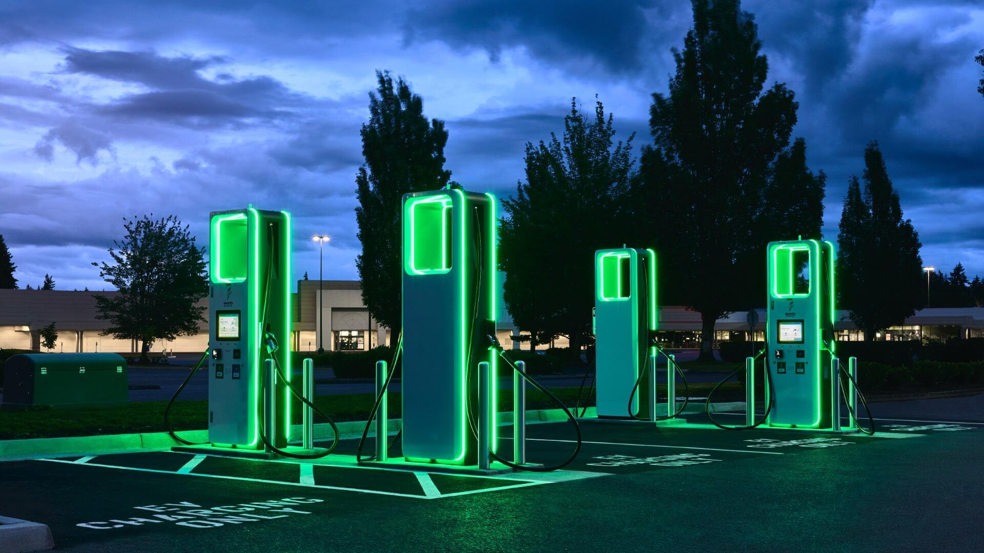 Finished project where electric car charges were installed, now fully illuminated at dusk