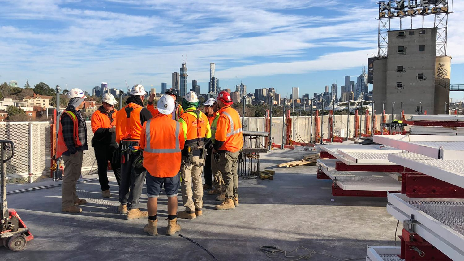 Group of individuals huddling on an empty jobsite.