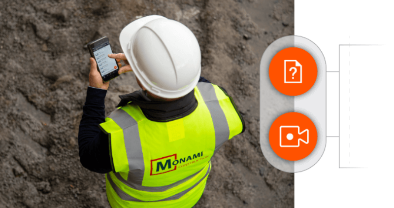 Construction worker using Procore software on mobile while on site