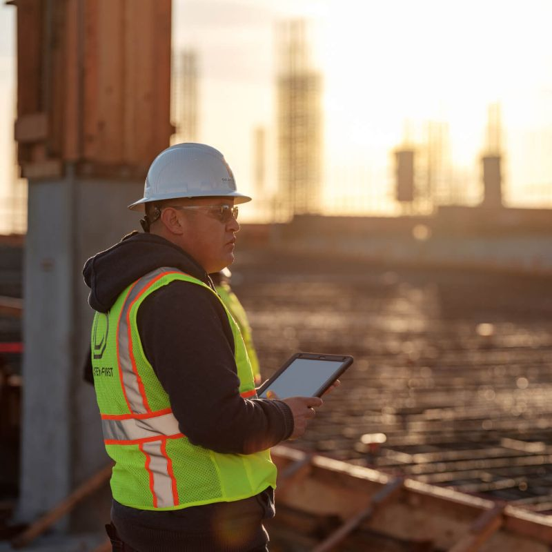 Construction worker using Procore on a tablet