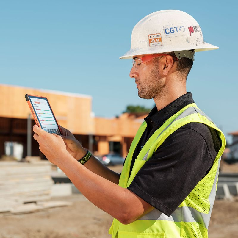 Construction worker using Procore on an iPad