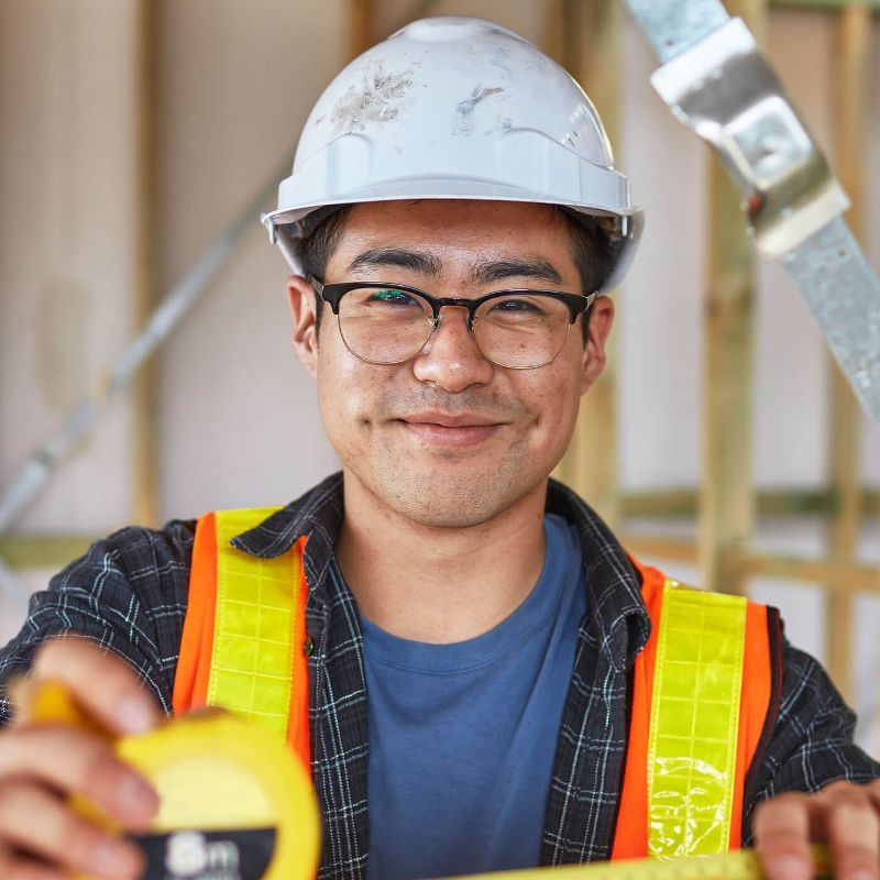 Construction worker smiling into camera wearing PPE