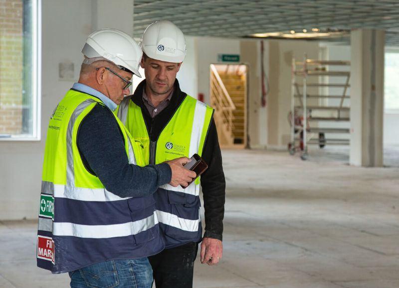 Construction worker colleagues looking at Procore software together on a device