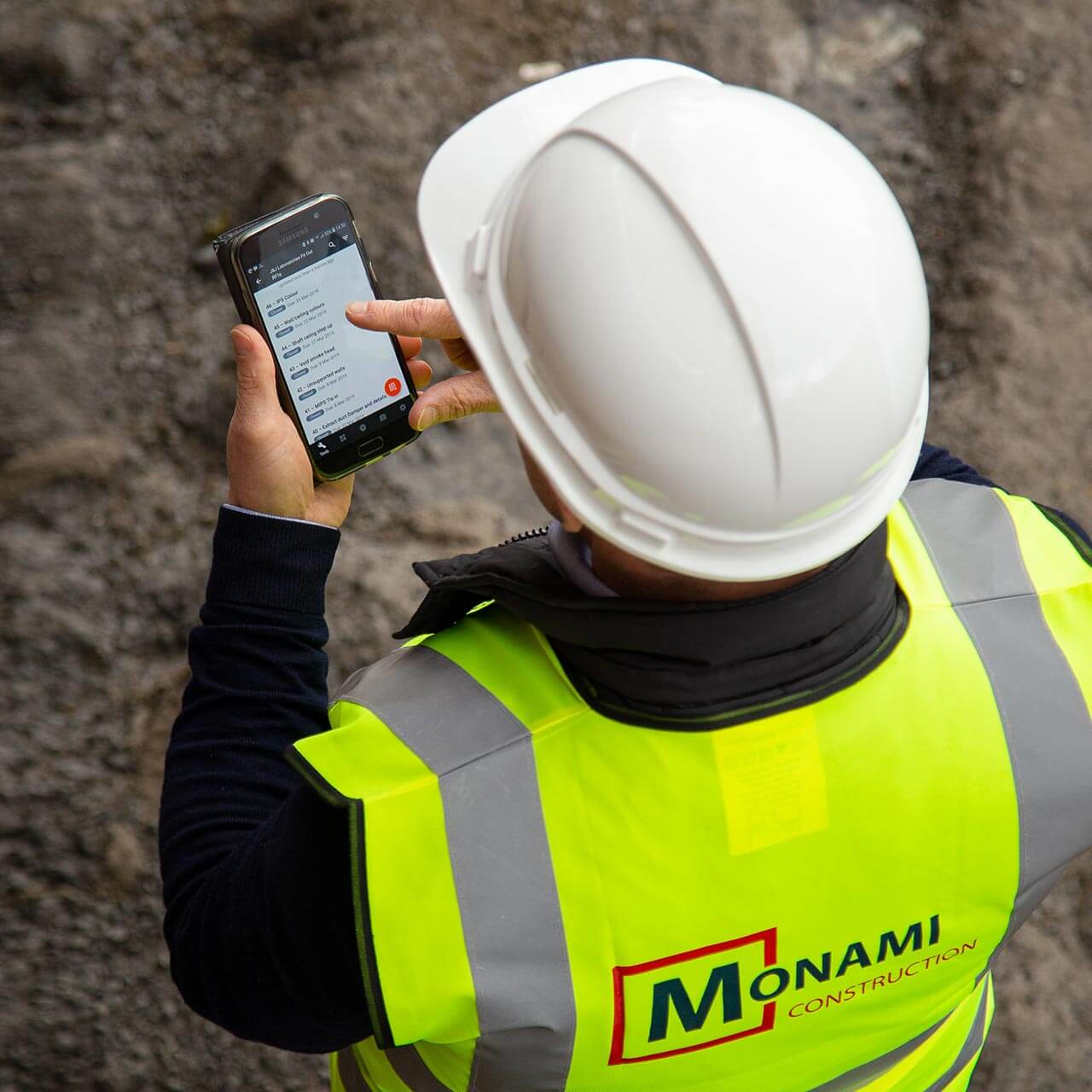 Construction Worker in PPE using Procore on a mobile device